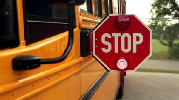 Side of school bus with red stop sign arm extended