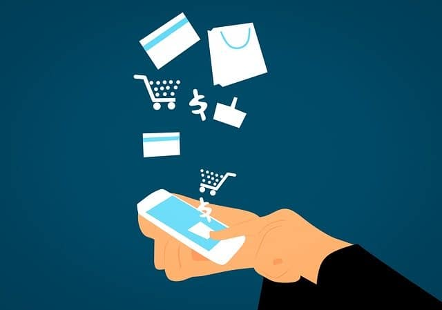 Graphic with a hand holding a smart phone with images of a shopping card, dollar sign, credit card flowing from it.